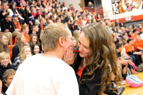 "Jake McBride and Samantha Tucker, freshmen, race to meet in the middle of the ""Lady and the Tramp"" relay at the Homecoming Assembly. Students who competed in this class competition had to eat a piece of licorice until they met. McBride surprised Tucker, and the entire student body audience, by sneaking in a kiss. ""I did not expect him to kiss me,"" she said. ""I was not happy and pushed him away."""