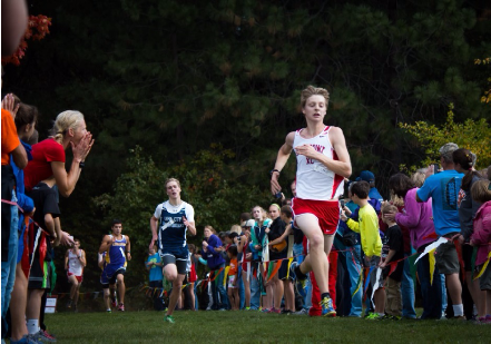 Andy McGinnis, a senior, enters the finishing chute at the home cross country meet. Coach Angie Brass cheers McGinnis on from the left hand side of the image. The audience is persuaded to care about this photograph and the story being told due to the setting of the home meet finishing chute and the connection between coach and athlete.