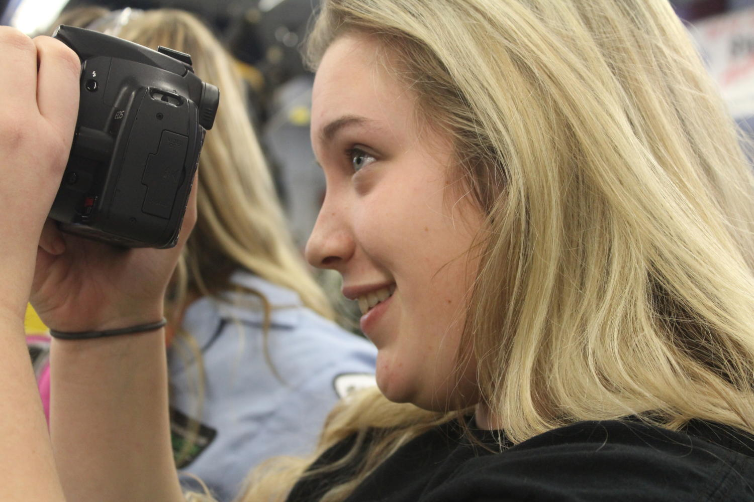 High school student Hailey Hasenyager focuses her camera. She is on her school's publication staff.
